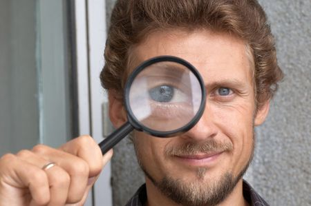 Portrait of a young man with a magnifying glass