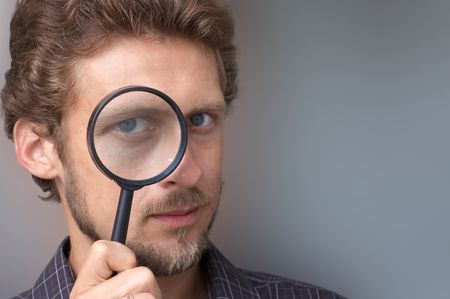 loupe: A portrait of a young man with a magnifying glass Stock Photo