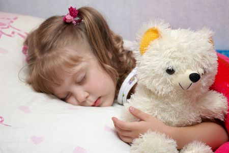A little girl sleeping with a toy