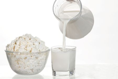 Fresh cottage cheese and milk in glass. White still-life. photo