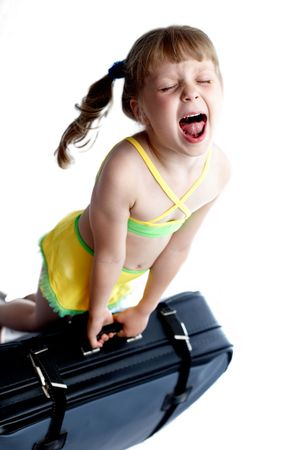 holidaymaker: A girl trying to lift up a heavy valise Stock Photo