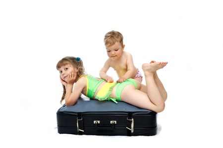 valise: Two girls playing on a black valise