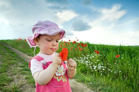 Nice -girl with red poppy on the lane amongst green field Stock Photo - 3281313