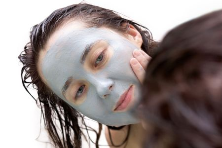 A girl putting a mud mask on her face photo
