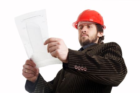 Construction foreman in red helmet checking drawings photo