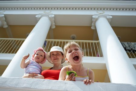 residental care: mother and her two daughters near a large house with columns Stock Photo