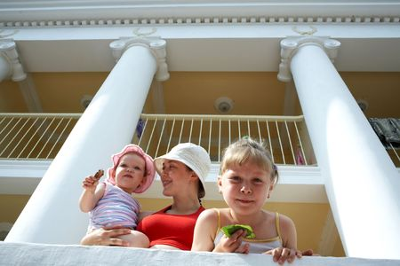 residental: mother and her two daughters near a large  with columns Stock Photo