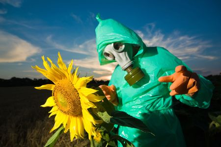 An image of man in gas mask on sunflower field photo