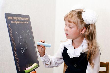 shool: An image of nice little girl in shool writing on chalkboard.