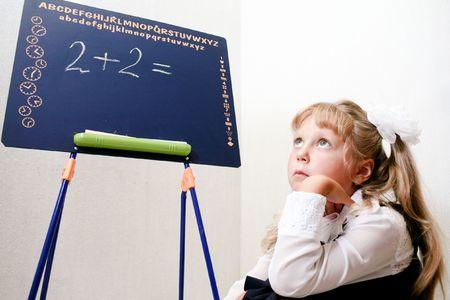An image of Little girl sitting near chalkboard. photo