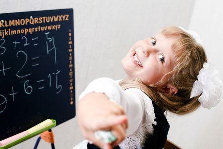 An image of Little girl standing near chalkboard.  photo