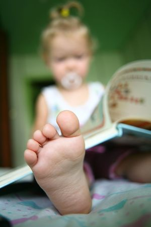 assiduous: An image of a baby reading a book Stock Photo