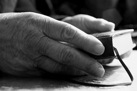 An image of old hands keep the Bible Stock Photo