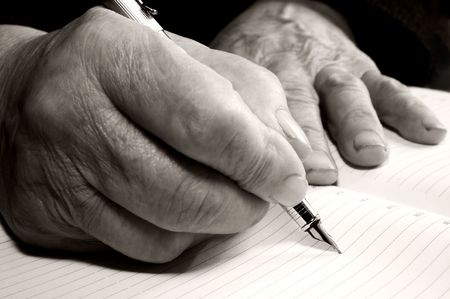 Old hands writing something with a pen in a notebook Stock Photo