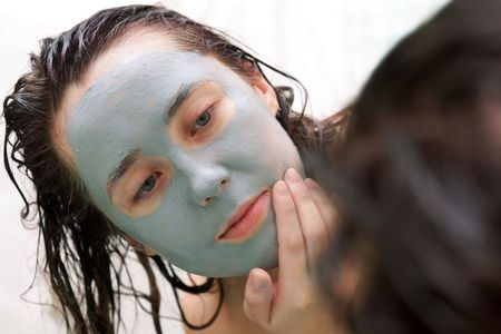 A woman putting a mud mask on her face photo