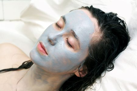 A nice woman putting a mud mask on her face photo