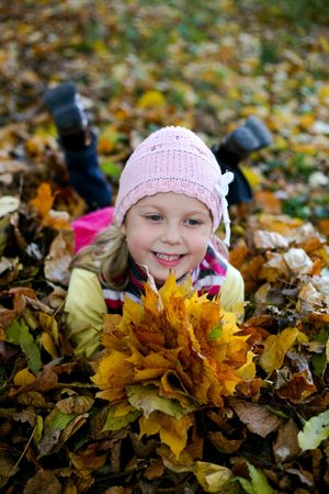 An image of nice child in leaves in autumn park photo