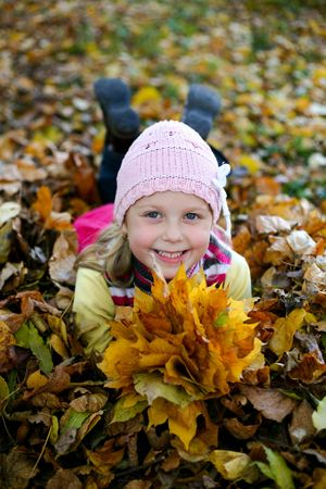 An image of nice child in leaves in autumn park