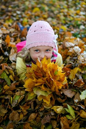 An image of little girl with yellow leaves in autumn park photo