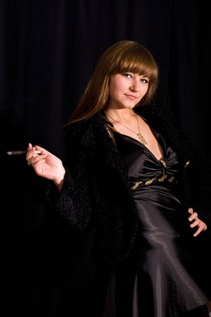 cigar smoking woman: An image of a woman in a black dress with cigar Stock Photo