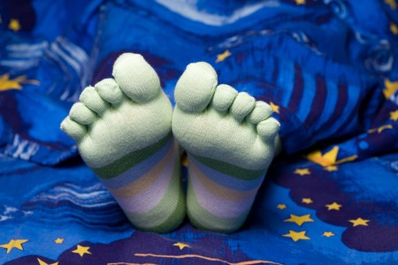 Stock photo: an image of funny feet in striped socks in bed Stock Photo - 4309195