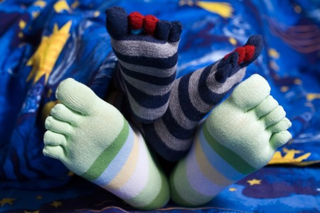 Stock photo: an image of two pairs of funny feet in striped socks photo