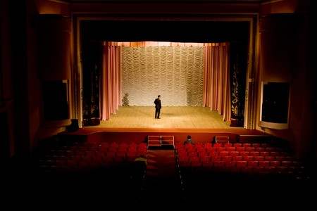 auditorium: Stock photo: an image of a man on the stage in empty hall