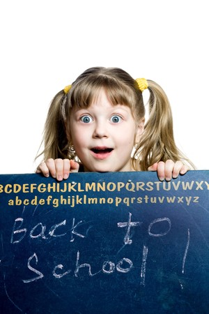 An image of a surprised schoolgirl looking from behind a blackboard Stock Photo