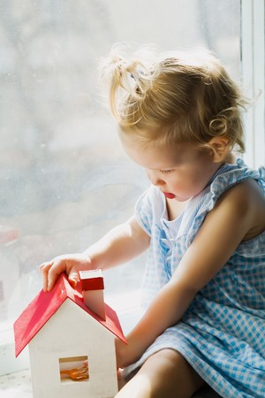 An image of a cute baby with little house