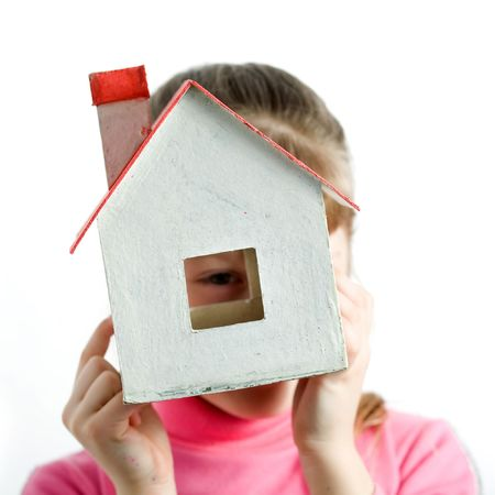 An image of a child looking into the window of little house