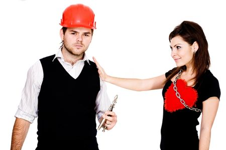 futility: A sad man in a red helmet with pliers and a pleased woman with his heart tied to her by a metallic chain Stock Photo