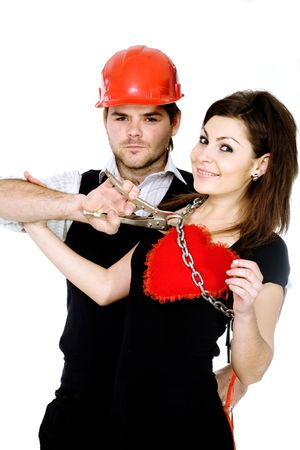 futility: A man in a red helmet and with pliers trying to releasie his heart captured by a woman