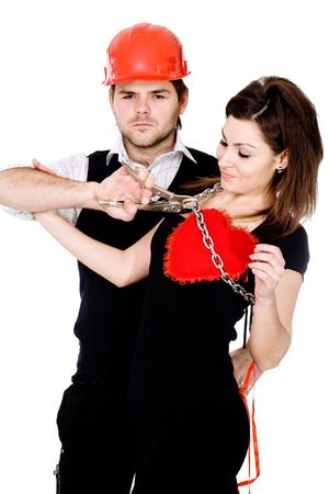 futility: A man in a red helmet and with pliers  trying  to release his heart captured by a woman