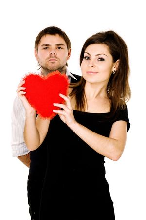 Enigmatically smiling charming woman with a big scarlet heart in her hands and a  man behind her back   photo