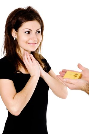 A pleasantly surprised and pleased young woman and man�s hands holding out a box with a wedding ring photo