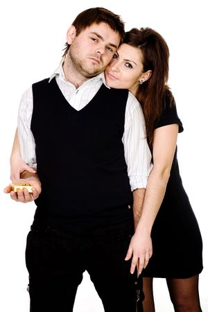 A brooding man with a wedding gift in a hand and a woman closely nestled to his back     photo