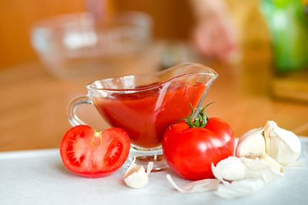 poignant: Appetizing  tomatoes and garlic while preparing a poignant sauce   Stock Photo