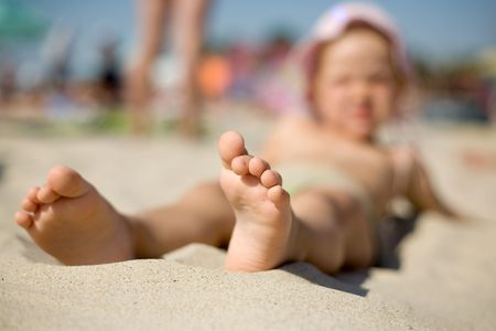 A  little girl on the sand with her feet close-up photo