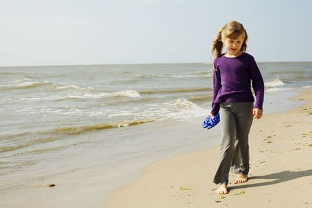 little girl barefoot: An image of a little girl walking along the seashore