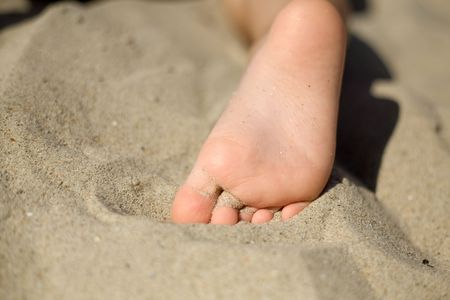 little girl barefoot: An image of little girls foot on the sand