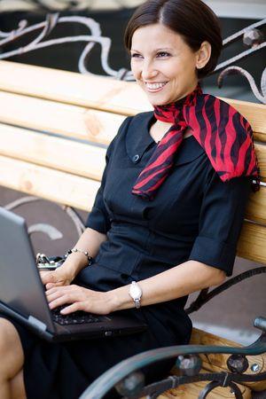 Una imagen de una mujer con un ordenador port�til en el banco de Foto de archivo - 5362784