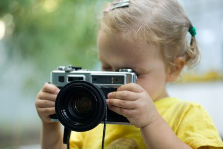 A beautiful little girl with a camera photo