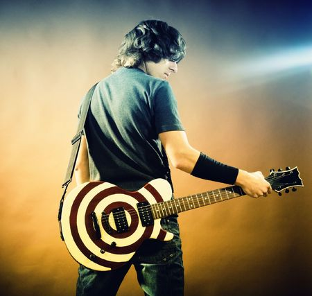 An crossprocess  image of a young man with guitar on black background Stock Photo - 5941855