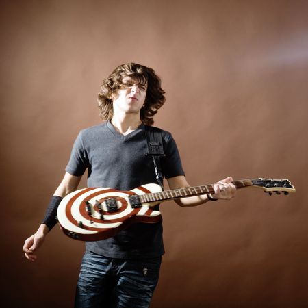 An image of a young man with guitar on black background Stock Photo