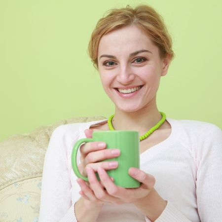 An image of happy woman with green cup photo