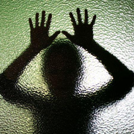 abuso: Una imagen de una silueta detr�s de vidrio