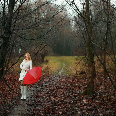 A woman with a red umbrella in autumn park photo
