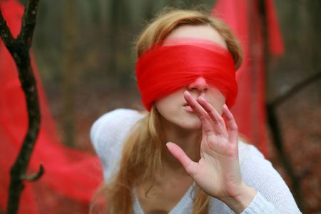 An image of blindfolded woman in the forest