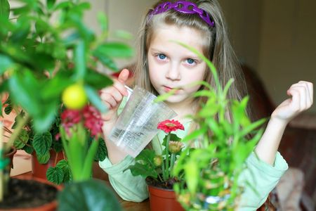 An image of a nice girl watering flowers photo