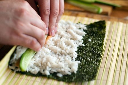 california roll: An image of man making california roll close-up